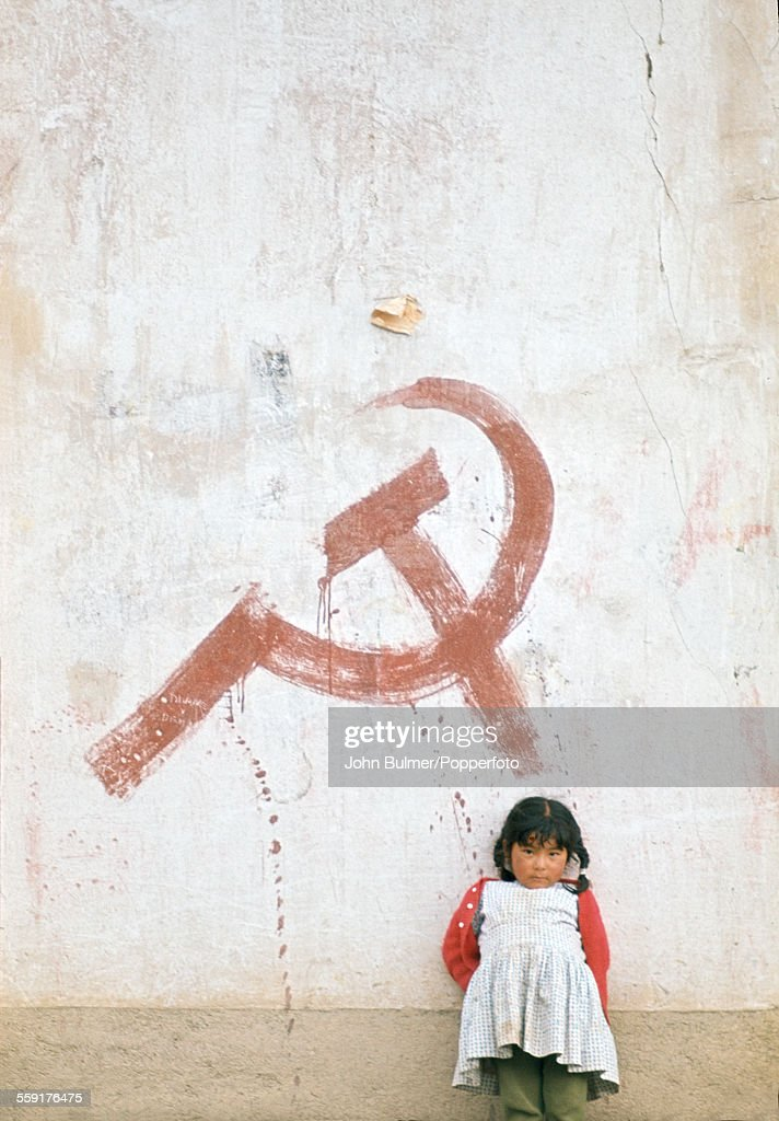 A little girl standing in front of a graffiti hammer and sickle in Bolivia circa 1983