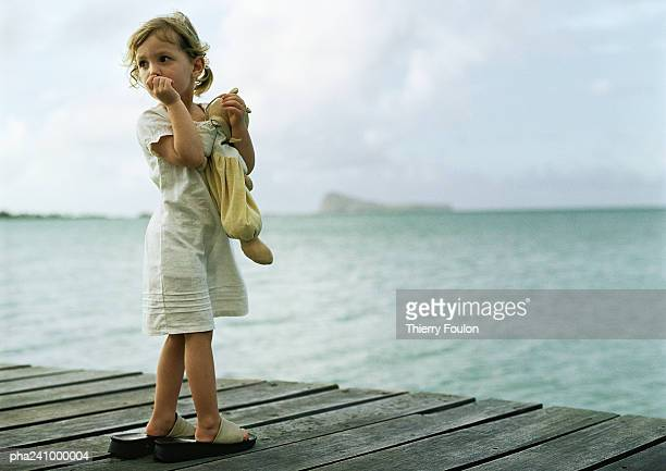 Little girl standing on dock, sucking thumb and looking over shoulder