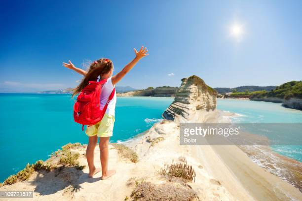 Little girl standing on rock with arms outstretched