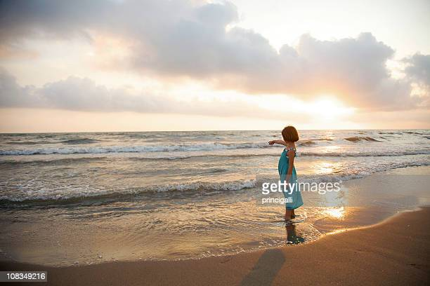 Little Girl Standing on the Beach at Sunset