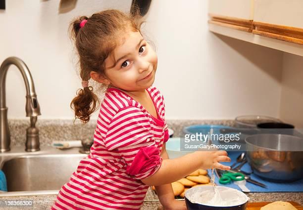 Little girl stirring frosting