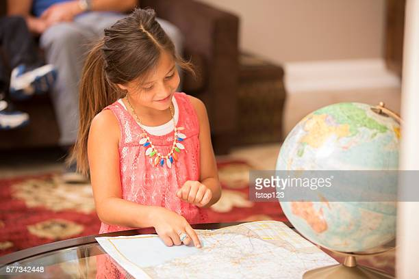 Little girl studies world maps. Finds family vacation destination.