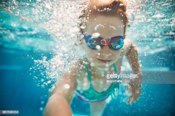 Little girl swimming underwater.