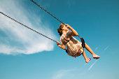 Kleines Mädchen schwingen gegen blauen Himmel