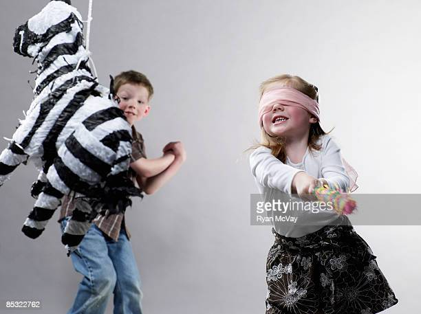 Kleines Mädchen schwingen im Piñata