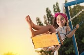 Little girl is swinging at play ground when sun is setting.