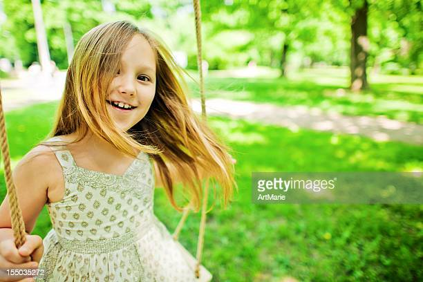 Little girl swinging in a park