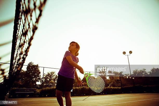 little girl swinging on tennis court