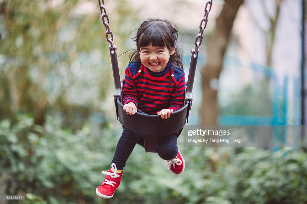 Little girl swinging on the swing joyfully : Stock Photo