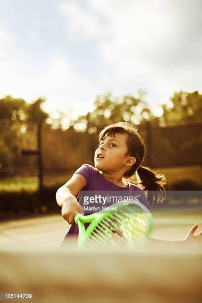 little girl swinging tennis racket