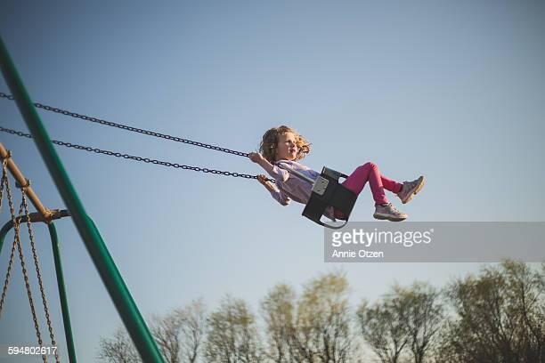 Little girl swings high into the sky