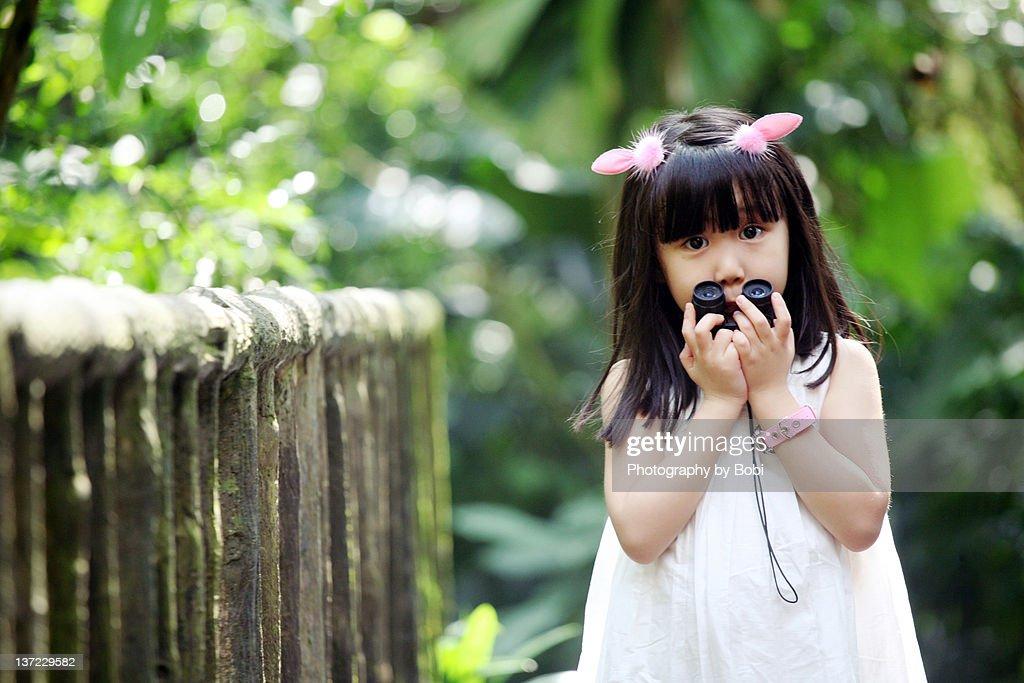 Little girl take telescope in Singapore zoo