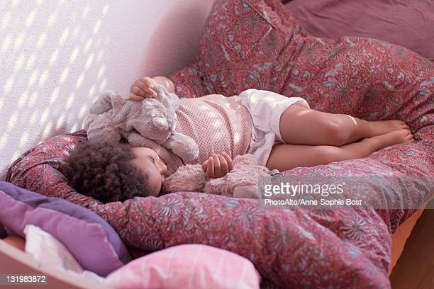 Little girl taking an afternoon nap with stuffed toy