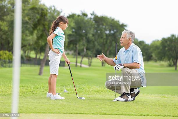 Little girl taking golf lessons from professional instructor