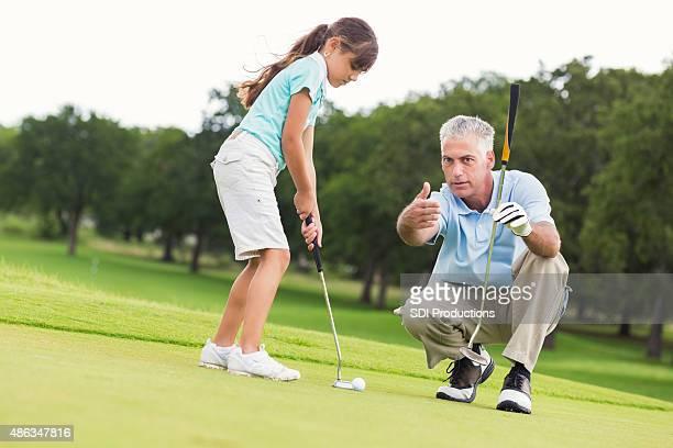 Little girl taking golf lessons from senior golf pro instructor
