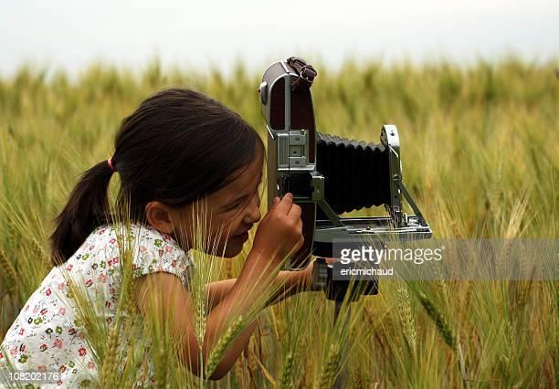 Petite fille prendre des photos dans le champ avec appareil photo Vintage
