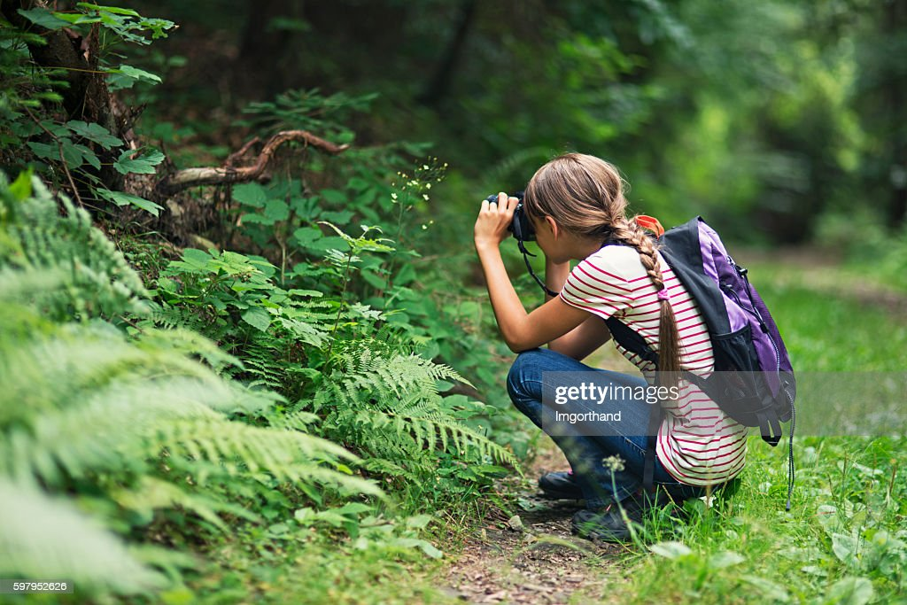Little girl taking photos in the forest : Stock Photo