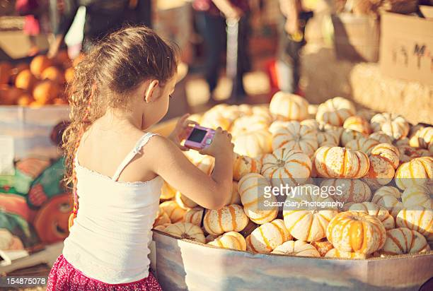 Little Girl Taking Pictures of Pumpkins