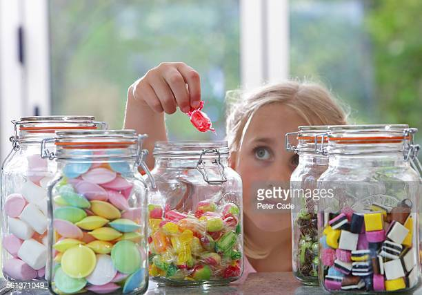 little girl taking sweet out of sweet pots .