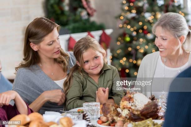 Meisje gesprekken met familie op tafel
