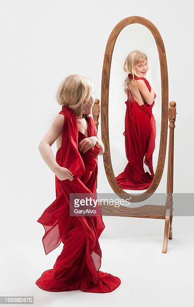 Little girl tangled in gown/playing dress up-reflection in mirror