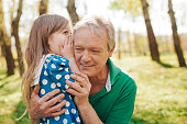 Adorable cute girl whispering to grandfather ear during the walk in park.