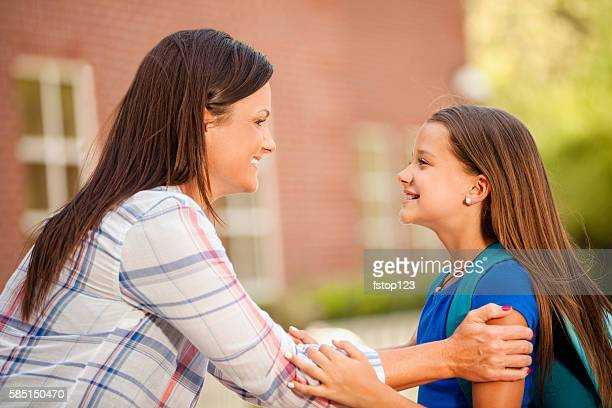 Little girl tells mom goodbye on first day of school.