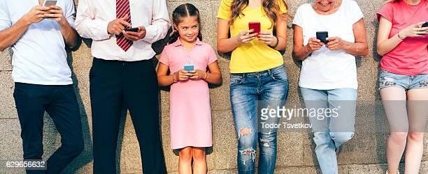 Little girl texting among adults