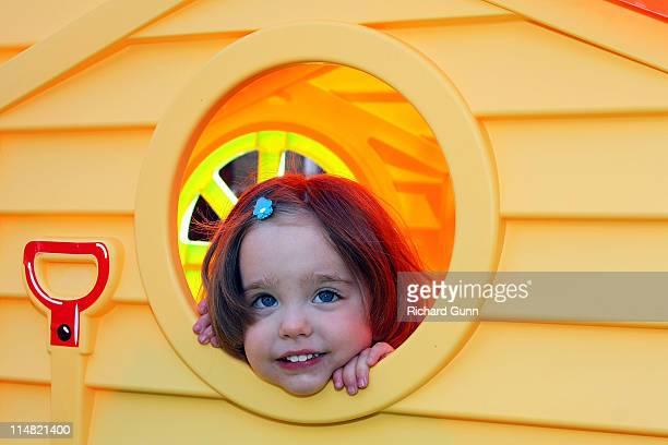 Little girl through wendy house window