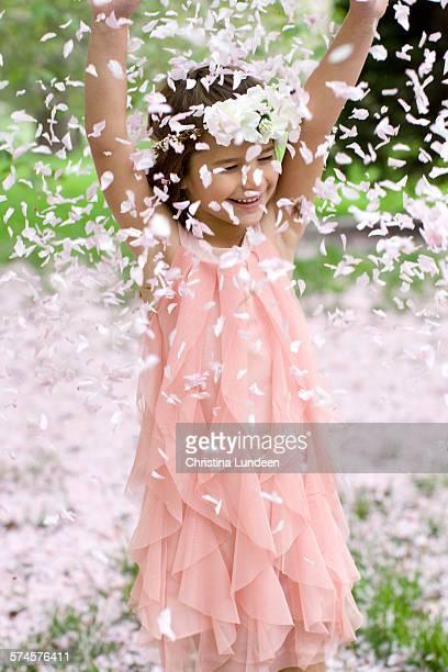 Little girl throwing flower petals