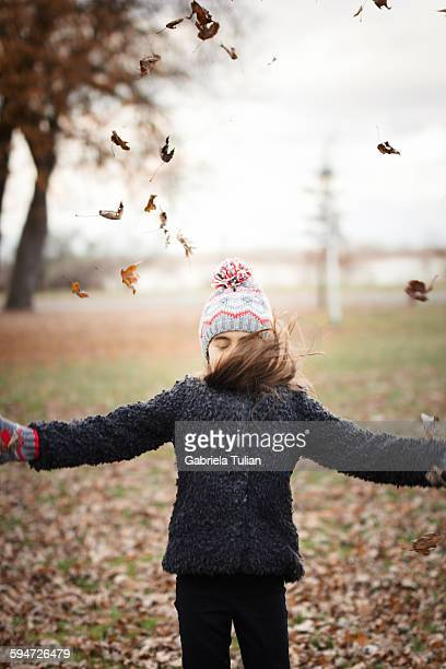 Little girl throwing leaves in the air in autumn