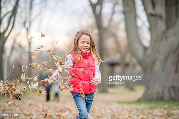 Petite fille jeter les feuilles