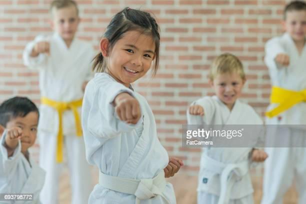 Petite fille jette un coup de poing à la pratique des Arts martiaux
