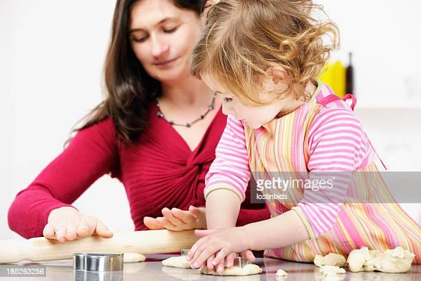 Kleines Mädchen/Kleinkind-Watching Mutter/Pflegekraft reisen, während Sie den Teig vorbereiten