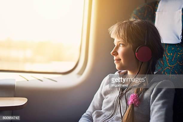 Bambina in viaggio in treno e ascoltare la musica.