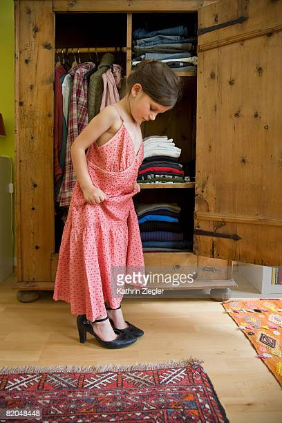 little girl trying on her mother's shoes and dress