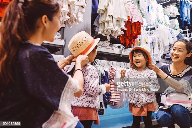 Little girl trying on straw hat with mom in shop
