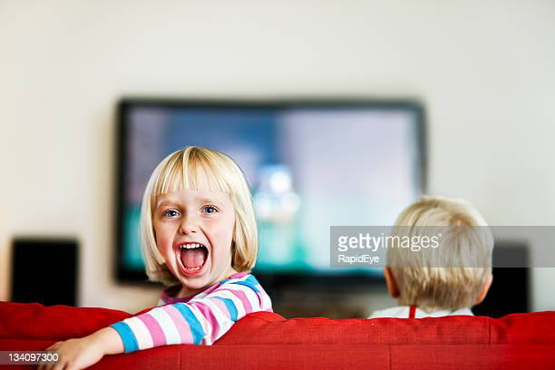 Little girl turns back from television and shouts excitedly