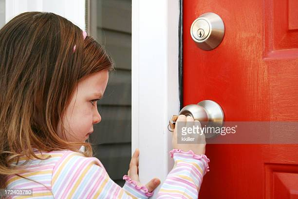 Little girl unlocking a red door