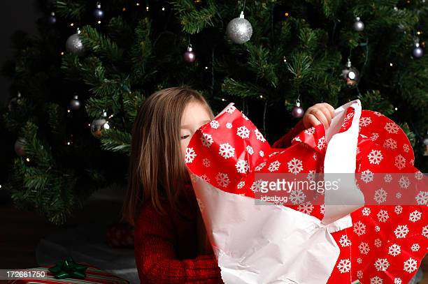 Little Girl Unwrapping Chirstmas Gift by Tree