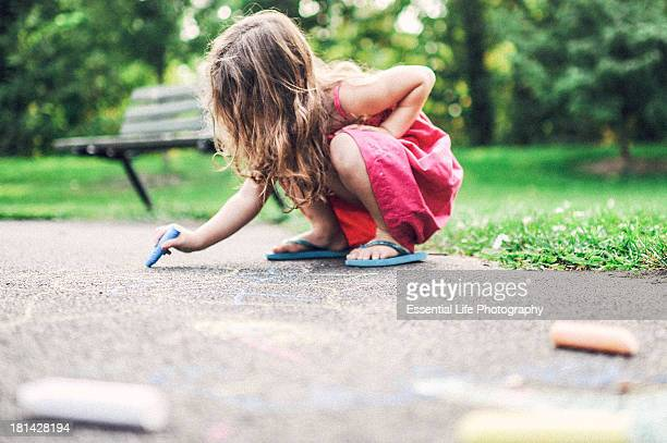 Little girl using chalk on cement