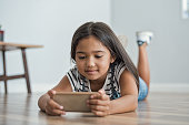 Little asian girl lying on floor using mobile phone to play. Multiethnic female child watching cartoon on smartphone at home. Childhood and moder technology concept.