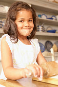 Little girl using rolling pin