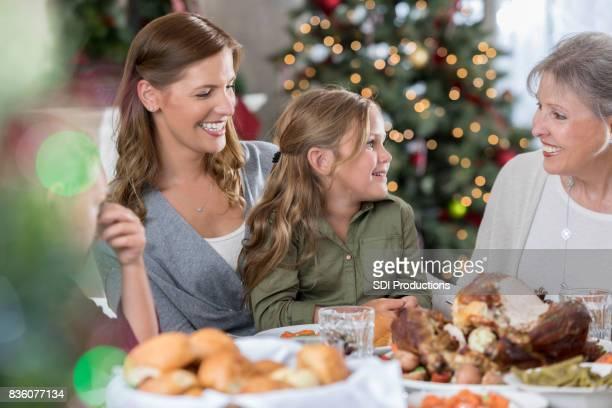 Kleines Mädchen besucht mit ihrer Mutter und Großmutter während Weihnachtsessen