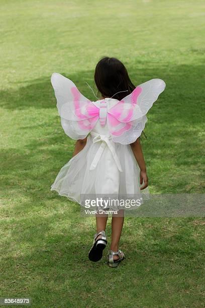little girl walking away with wings