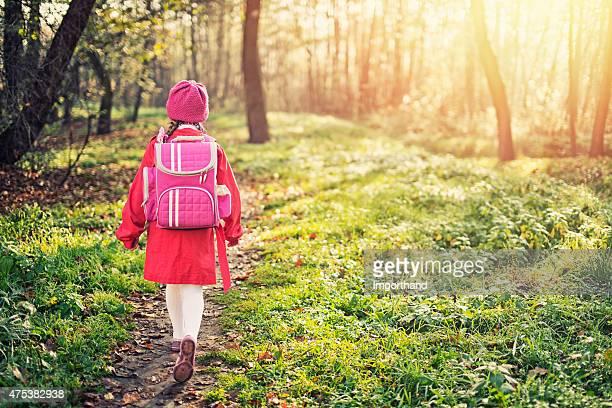 Petite fille marcher retour à l'école avec un sac à dos