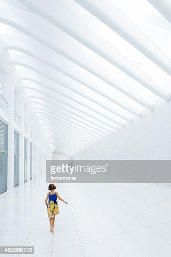 Little Girl walking barefoot on white marble corridor