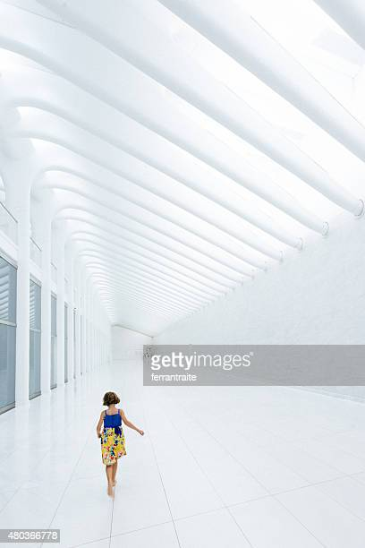 Bambina camminare a piedi nudi su bianco marmo corridoio