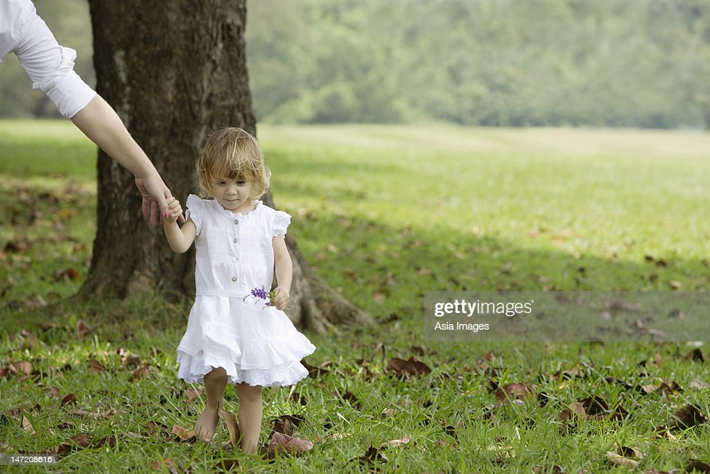 Little girl walking, holding woman's hand : Stock Photo