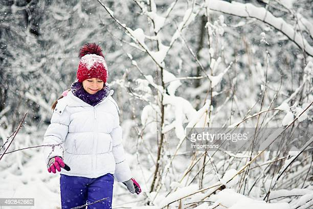Little girl walking in snow in winter forest